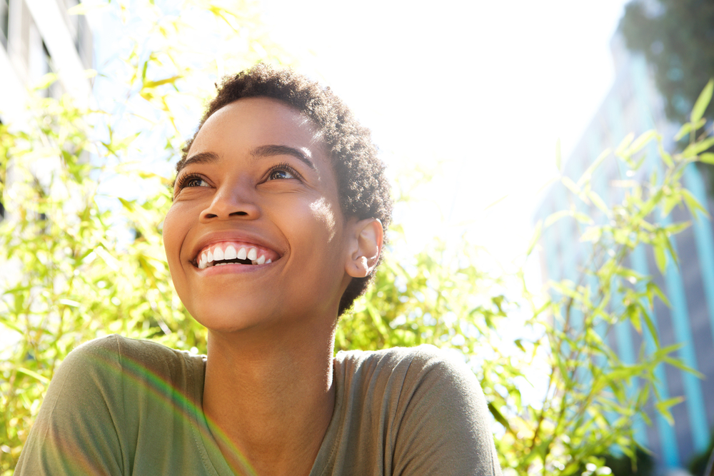 A young woman looking up and smiling with the sun shining behind her