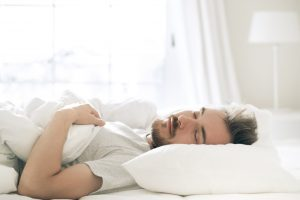 A man sleeping on his back in white linens
